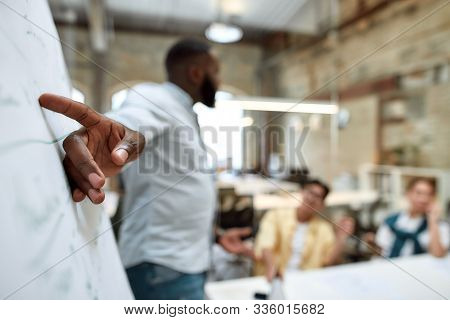 Business Concept. Young Afro American Businessman Pointing At White Blackboard And Explaining Someth