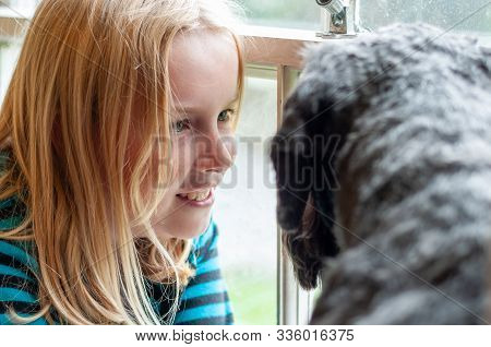 Pretty Blonde Girl Happily Gazing At Her Black Dog In Front Of A Window