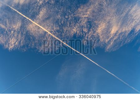 A Contrail Due To An Airliner Passing Earlier Is Diagonally Aligned In The Blue Sky With Cirrus And