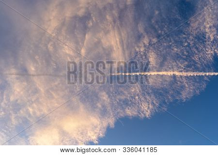 Cirrus And Cirrocumulus Clouds Together With A Contrail By An Earlier Passing Airplane Is In The Cen