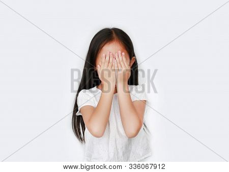 Portrait Of Little Asian Girl Closing Hid Eyes By Hand Isolated On White Background. Kid Is Crying A
