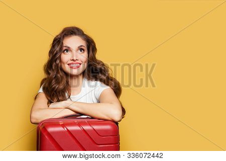 Tourist Woman With Red Suitcase Looking Up On Yellow Background. Pretty Girl Passenger Traveling Abr
