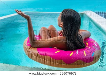 Rainy day on Caribbean all inclusive resort hotel vacation. Ruined summer holidays because of rain tropical storm. Travel cancellation insurance. Sad woman on bad holiday floating in swimming pool.