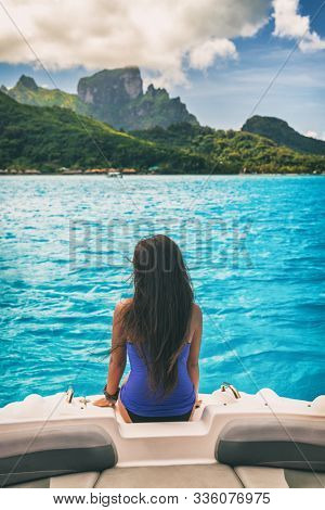 Luxury travel boat trip excursion woman tourist relaxing on idyllic blue lagoon cruise vacation travel holiday in Bora Bora island, Tahiti, French Polynesia. Girl from behind with long hair.