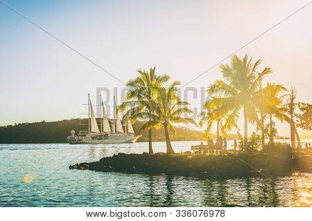 Luxury travel cruise ship sailing away in French Polynesia Tahiti Bora Bora island sunset landscape. Honeymoon famous destination idyllic tropical islands.