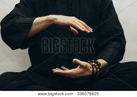 A Man In Black Shirt Sitting And Doing Qigong. Hands Direct Energy. Prayer, Gratitude.practicing Mon