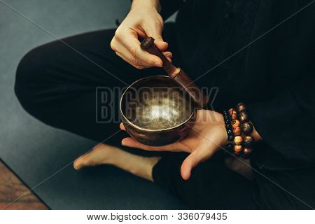 Top View Of A Man Sitting In A Lotus Position With A Rosary On His Hand Playing On Singing Bowls. Re