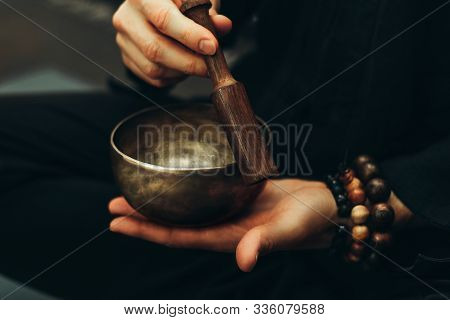 Close-up Of Hands With Rosary Playing On Singing Bowls. Relaxation And Meditation. Alternative Medic