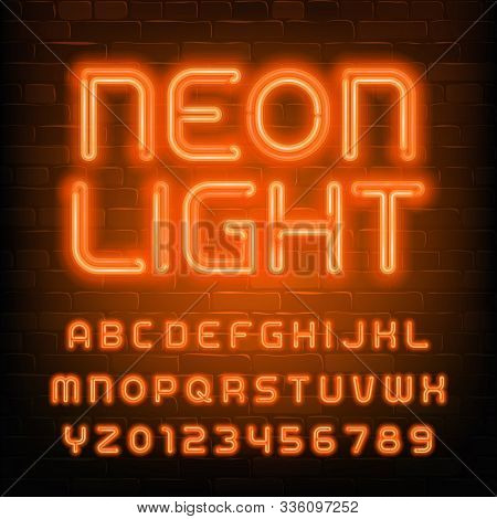 Neon Light Alphabet Font. Simple Orange Neon Letters And Numbers. Brick Wall Background. Stock Vecto