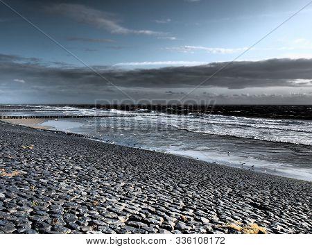 Stone Dam And Beach Under Dark Clouds Near Westkapelle, Zeeland, The Netherlands