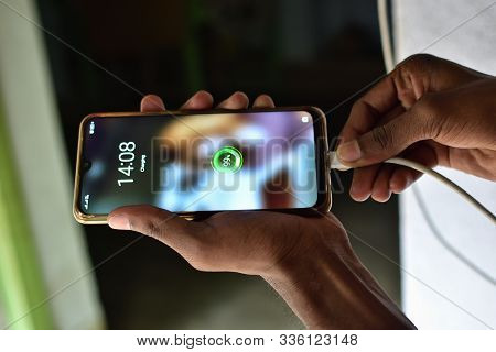 Charger With Device On Wooden Desk. Mobile Charging Concept . Concept Of Mobile Phone Mania. Mobile