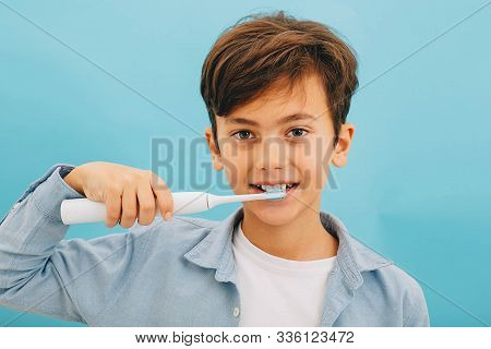 Mixed Race Little Boy Cleaning Teeth With Sonic Toothbrush On Blue Background. Perfect Removing Plaq