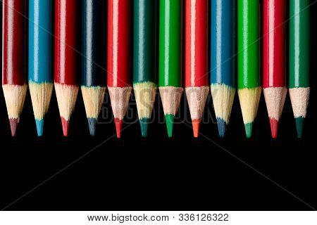 Colored Pencils On Black Background Pointing Down Room For Text Advertisement Art Project June Septe