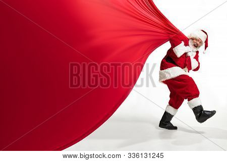 Santa Claus Pulling Huge Bag Full Of Christmas Presents Isolated On White Background. Caucasian Male