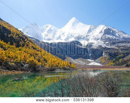 View Of Snow Covered Mountain Peaks, Autumn Leaves And Green Lake In Yading Nature Reserve, Sichuan,