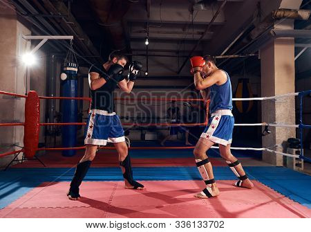 Young Boxer Practicing Kickboxing With Sparring Partner In The Ring At The Sport Club