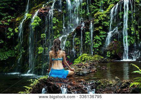 Young Woman Sitting On The Rock, Practicing Yoga Near Waterfall. Hands In Gyan Mudra. Banyu Wana Ame