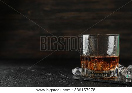 Glass Of Whiskey And Ice Cubes On Black Background, Space For Text