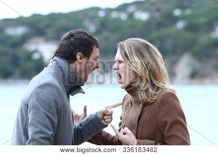 Angry Man And Woman Arguing And Shouting Each Other In Winter On The Beach