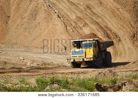 Big Yellow Dump Truck Transporting Sand In An Open-pit Mining Quarry. Mining Quarry For The Producti