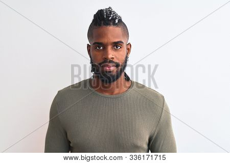 African american man with braids wearing green sweater over isolated white background with serious expression on face. Simple and natural looking at the camera.