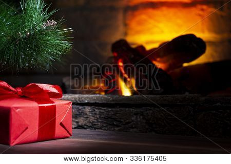 Red Gift Box Under The Christmas Tree On A Wooden Table Near A Biofireplace. Christmas Composition,