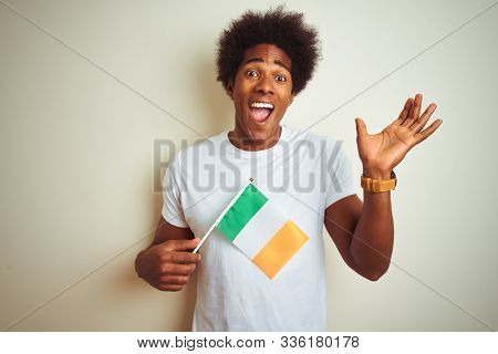 Young african american man holding Ireland Irish flag standing over isolated white background very happy and excited, winner expression celebrating victory screaming with big smile and raised hands