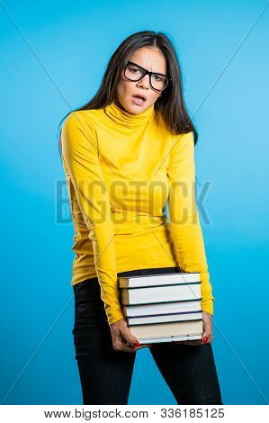 Hispanic Student Is Dissatisfied With Amount Of Homework And Books. Girl With Books, She Is Annoyed,