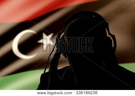 Silhouette Of A Man Wearing Headphones On The Background Of The Flag Of Libya, Eavesdropping On A Co