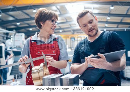 Man and women worker in the metalworking industry with workpieces