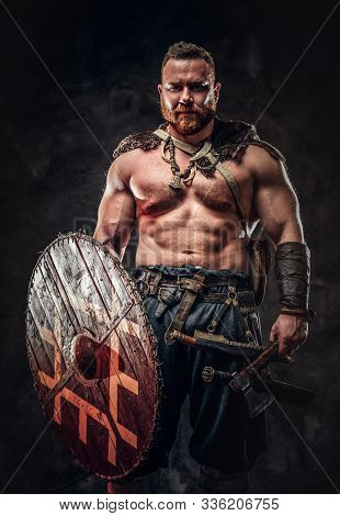 Severe Barbarian In Warrior Clothes, Posing On A Dark Background.