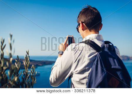 Santorini Traveler Taking Photo Of Caldera From Fira Or Thera, Greece On Phone. Tourism, Traveling,
