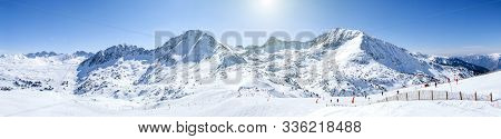Winter High Mountain Chains Landscape On A Sunny Day. Long Ski Slopes, Lifts, Skiers, Snowboarders A
