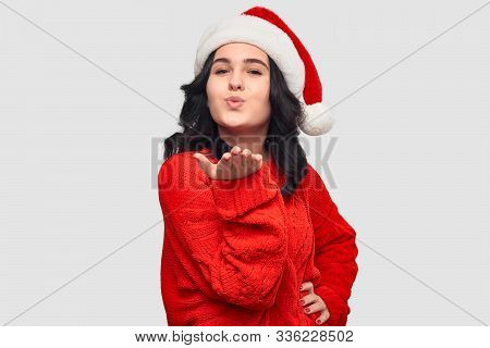Excited Brunette Girl In A Red Sweater And Santa Hat Sending Air Kiss Looking At The Camera. Merry C