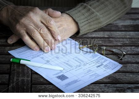 Hands Of Old Senior Man Fills In Utility Bills On Wooden Table. Planning Month Budget, Calculating E