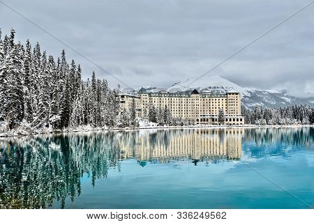 Mountain Lodge Resort In Winter Forest By Turquoise  Calm Alpine Lake With Snow Capped Mountains Beh