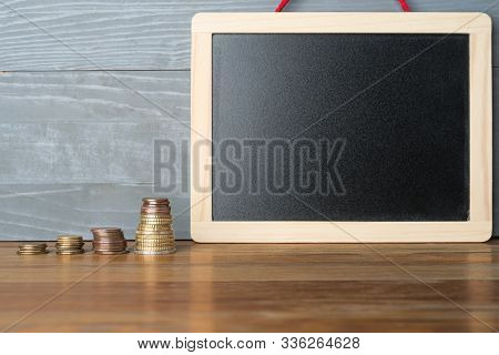 Ascending Stacks Of Coins With Blank Blackboard. Education Expenses Or Rewards Abstract Concept.
