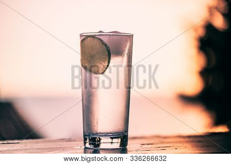 Cocktail Glass With Gin Tonic And A Lime And Ice Cubes On A Balcony With Scenic And Magnificent View