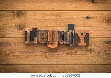 Legacy, single word written with vintage letterpress printing blocks on rustic wood background.