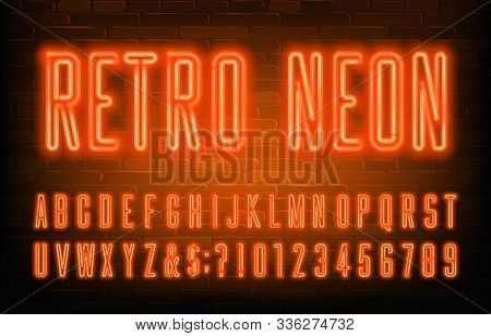 Retro Neon Alphabet Font. Condensed Orange Neon Letters And Numbers. Brick Wall Background. Stock Ve