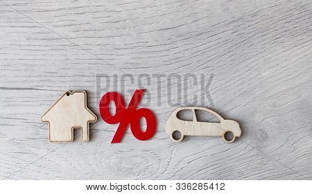 Wooden car and house model with percent sign. The concept of low interest rates on mortgage loans or rentals. The percentage of real estate sales. Tax interest. Loan secured.