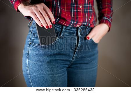Girl Puts Or Takes Out A Phone In A Black Case From Her Pocket, Close Up