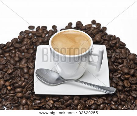 Espresson on a lot of coffee beans over a white background. poster
