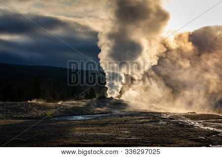 Old Faithful, Famous Geyser Of Yellowstone National Park, Wyoming, Usa, Exploding Hot Smoke In The A