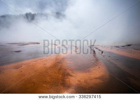 Smoke Covered Orange Pond Of Grand Prismatic Spring, Famous Geyser Basin In Yellowstone National Par