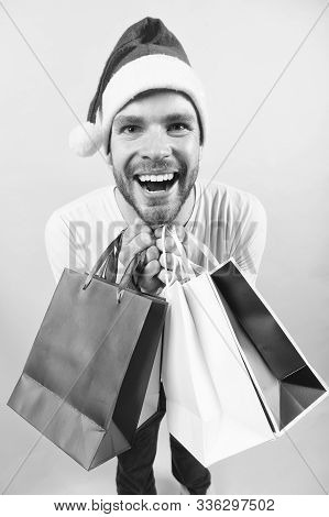 Man Santa Hold Shopping Bags On Orange Background. Macho Shopper In Xmas Hat Smile With Paperbags. W