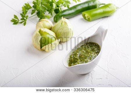 Tomatillo Salsa Verde. Bowl Of Spicy Green Sauce On White Table, Mexican Cuisine.