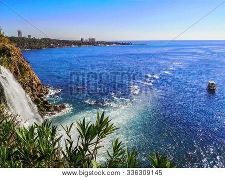 Tourist Boat Near Duden Waterfall On The Background Of Lara Beach In Antalya, Turkey. Beautiful Medi