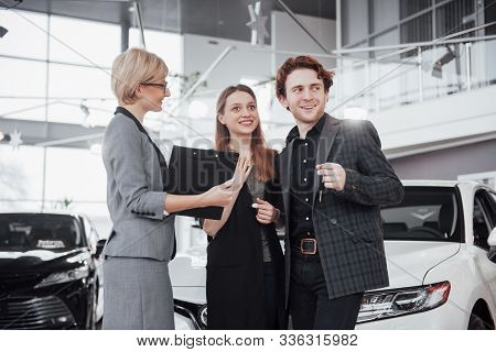Buying Their First Car Together. High Angle View Of Young Car Salesman Standing At The Dealership Te