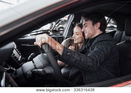 Making Their Decision. Beautiful Loving Couple Sitting In A New Car Together At The Dealership Hands